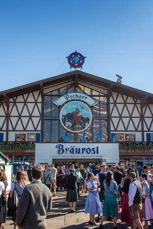 wiesn: Facade and entrance of the Braeurosl beer tent with people standing in front