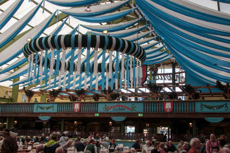 wiesn: Inside the Ochsenbraterei beer tent at Oktoberfest with people celebrating and drinking beer