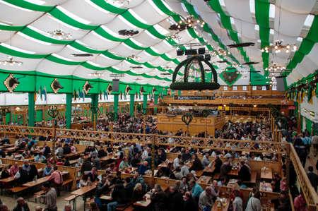 personas celebrando: Inside the Armbrustschuetzenzelt with people celebrating Oktoberfest