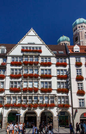 our people: The Hirmer house with its beautiful decoration is the largest mens fashion house in the world, in the background are the towers of the Frauenkirche (Cathedral of Our Dear Lady and unidentified people are walking along Editorial