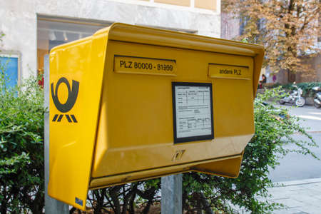 letterbox: Typical German yellow letterbox in Munich with two slots divided by postal code (for local and for global deliveries)