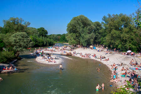 The Isar river in Munich with many unidentified people on a sunny day taking a sunbath