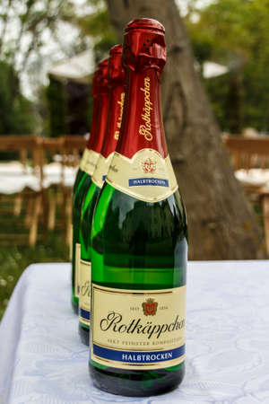 Four bottles with sparkling wine in a row (Rotkaeppchen brand) and chairs in the background