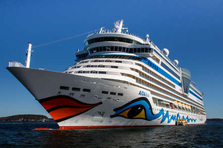 The cruise ship AIDA Diva with it's characteristic logo of lips and eyes on both sides of the ship in the bay of Bar Harbor (Maine, USA)