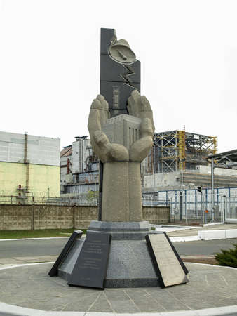 Rescuers memorial in front of the Chernobyl nuclear power station with damaged reactor block 4 in the exclusion zone