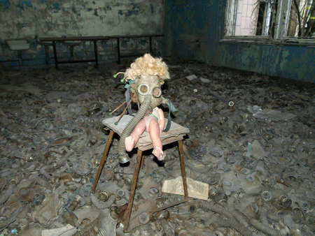 exclusion: Room full of gas masks with a doll on a chair in the ghost town Pripyat in the Chernobyl Exclusion Zone which was established after the nuclear disaster in 1986