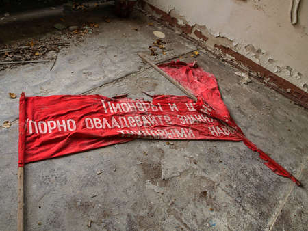 exclusion: Red flag lying on the ground of a building in the ghost town Pripyat in the Chernobyl Exclusion Zone which was established after the nuclear disaster in 1986