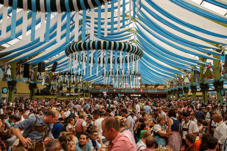 Munich, Germany - September 24, 2016: Inside the Ochsenbraterei beer tent at Oktoberfest with people celebrating and drinking beer Editorial