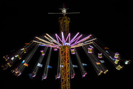 Munich, Germany - September 26, 2015: Carousel in motion with people flying through the air on Theresienwiese