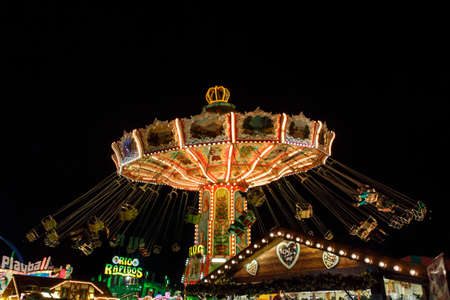Munich, Germany - September 26, 2015: Nightshot of the Wellenflug carousel in motion at Oktoberfest on Theresienwiese