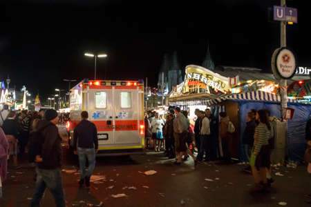 Munich, Germany - September 26, 2015: Emergency rescue service at the main street of the Octoberfest in Munich at night with an ambulance vehicle passing by