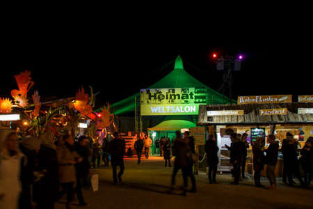 Munich, Germany - November 30, 2016: Tollwood winter festival and christmas market in Munich during the evening hours with illuminated tents and bars Editorial
