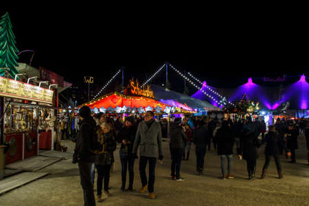 Munich, Germany - November 30, 2016: Tollwood winter festival and christmas market in Munich during the evening hours with illuminated bars