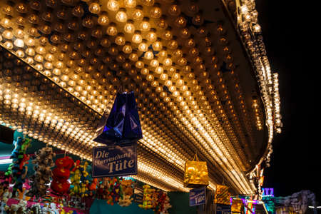 Munich, Germany - September 26, 2015: Illuminated roof of a sales stall at Oktoberfest with bags hanging from the roof saying Publikacyjne