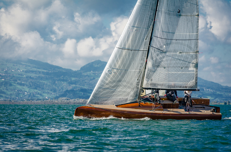 Wooden modern racing sailboat going upwinds