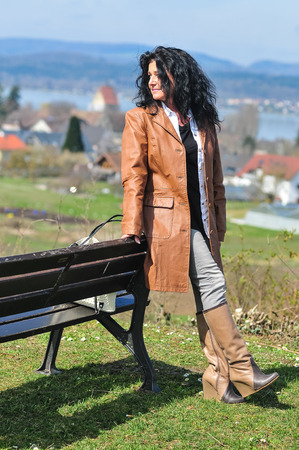Fourty-somthing lady good looking brunette sporty personality in brown leather enjoying the sun