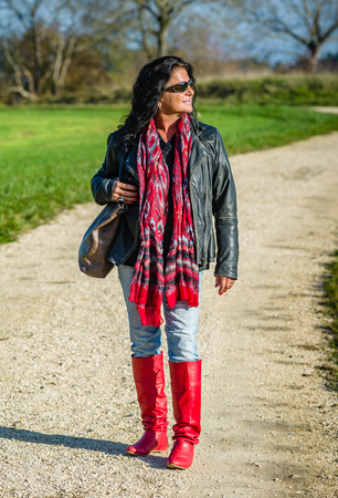 Fourty-somthing lady good looking brunette sporty personality in red boots taking a hike Stock Photo