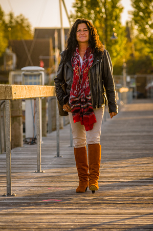 Fourty-somthing lady good looking brunette sporty personality wering black leather jacket and brown knee high boots 写真素材