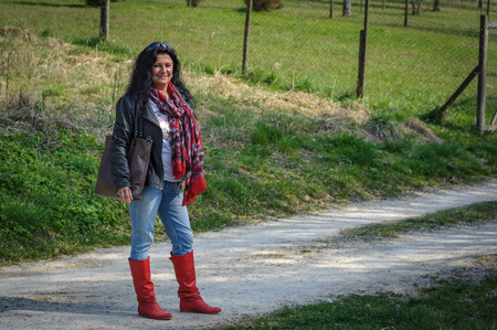 Fourty-somthing lady good looking brunette sporty personality countryside with red boots