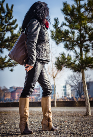 Fourty-somthing lady good looking brunette sporty personality wering black leather jacket and pants posing in the city