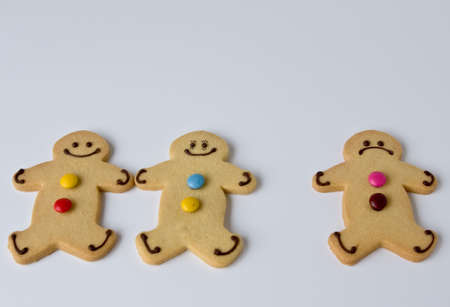 copule: Three shortbread figures demonstrate that three is often a crowd Stock Photo