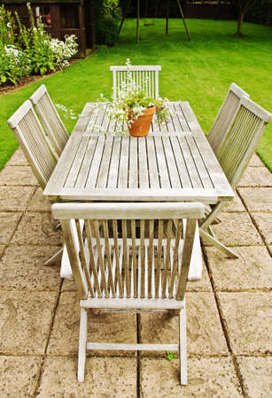 kept: A weathered garden table and chairs in a beautiful garden setting Stock Photo