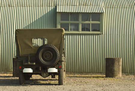 wartime: A wartime jeep is parked outside a period military building
