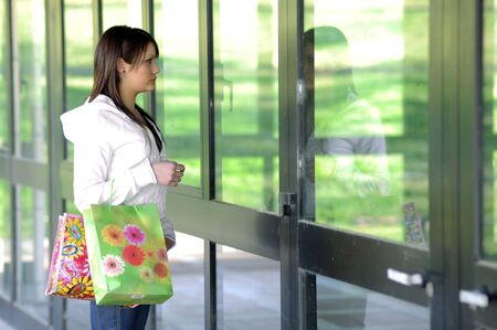 young woman with shopping bags looking a showcase photo