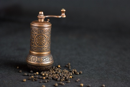 Vintage still life with brass pepper mill standing on the grey background