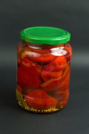 Canned red pepper in the glass on the black background photo