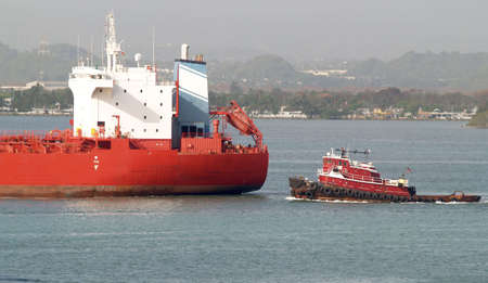 Red tug boat approaching to assist tanker.       Stock Photo