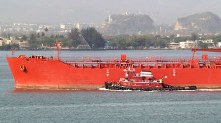 Red tug boat assisting large vessel out of port.