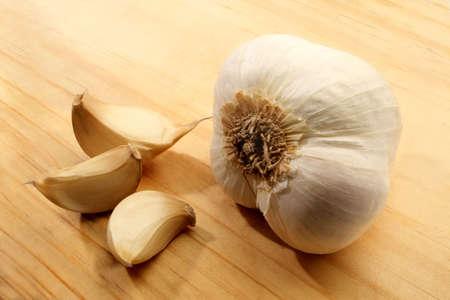 alliaceae: Garlic cloves displayed on a wooden cutting board.