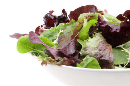 Organic mixed salad greens in a white bowl.