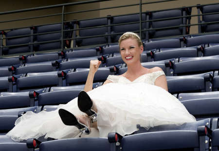 Model wearing wedding gown cheering in a baseball stadium.