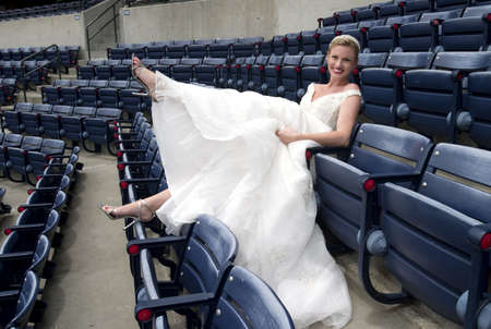 Model wearing wedding gown posed in a baseball stadium.