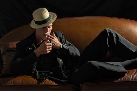 Elegant fashion man lighting a cigarette resting on the sofa photo