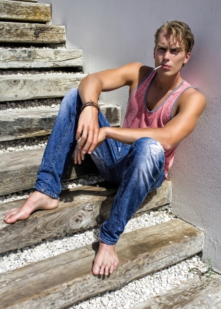 Young boy sitting on the steps smoking photo