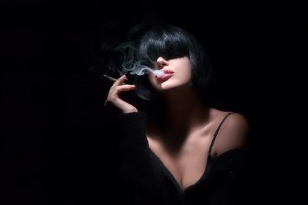 beautiful bangs: Young woman smoking a cigarette