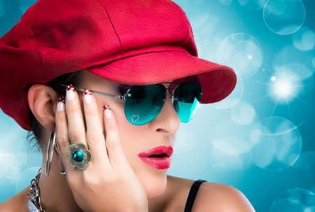 Portrait of fashionable hip hop girl with red cap, blue glasses and beautiful manicure photo