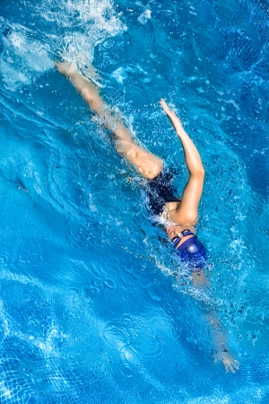 swimming competition: Young woman swimming in freestyle