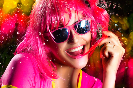 Portrait of beauty party girl with pink wig and glasses expressing happiness Stock Photo