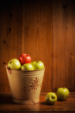 Bucket of green and red apples on wooden background photo