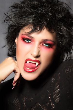 Beautiful young woman with fancy makeup, fangs and wolf lenses