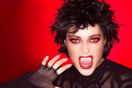 Beautiful portrait of young woman with fancy makeup, fangs and wolf lenses