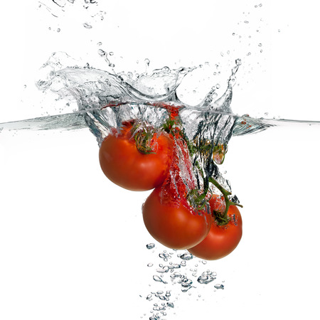 Closeup of fresh and health tomatoes falling into clear water with big splash isolated on white background