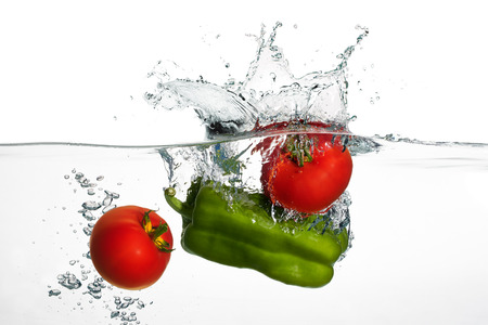 Closeup of fresh tomatoes and green Pepper falling into clear water with big splash isolated on white background