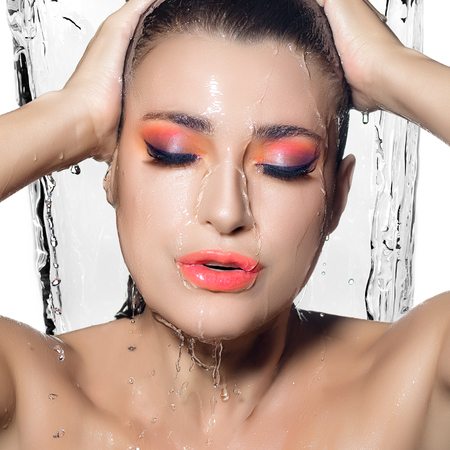 Fashionable Fluor make-up under flowing water. Closeup portrait of beautiful woman face with water falling down. photo