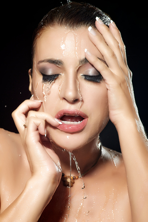 Sensuality woman face with water falling down. Beauty and fashion make-up under flowing water.  photo