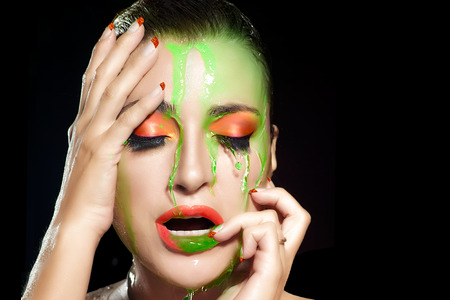 Sensual woman face under flowing water. Colorful makeup explosion.  photo